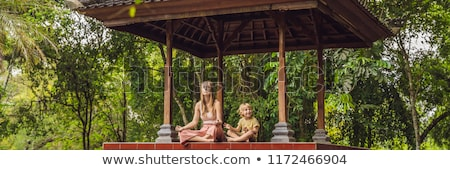 Mom and son meditate practicing yoga in the traditional balinesse gazebo BANNER, long format Stock photo © galitskaya