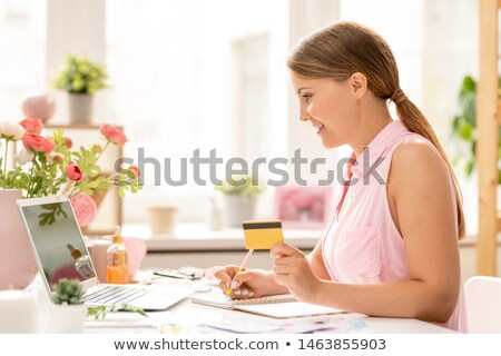Pretty girl with plastic card going to buy something in online shop Stock photo © pressmaster