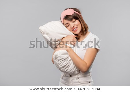 Happy girl in sleep-mask keeping her head on pillow while napping Stock photo © pressmaster