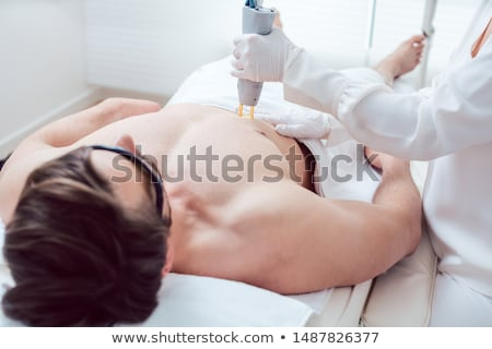 Cosmetologist using laser to remove chest hair of man Stock photo © Kzenon