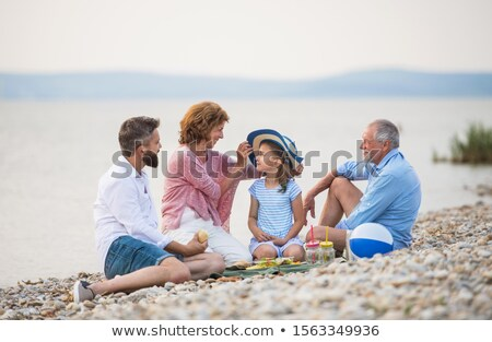 Front view of happy multi-generation family walking and having fun on beach in the sunshine Stock photo © wavebreak_media
