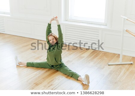 Satisfied redhead young female athlete practices yoga, makes splits exercises, wears sportswear and  Stock photo © vkstudio