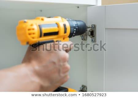 close up man holding cordless screwdriver machine and screws lie Stock photo © snowing