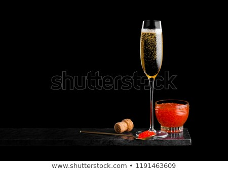elegant glass of yellow champagne with red caviar on golden spoon and glass container of caviar on m stock photo © denismart