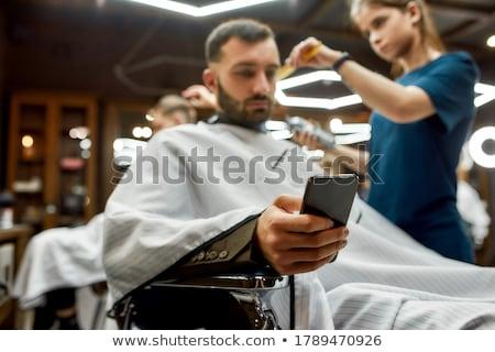 Hand of a barber using scissors while trimming Stock photo © Kzenon