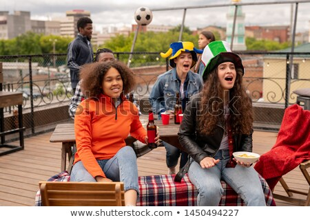 Excited girls with beer and snack chering for their football team Stock photo © pressmaster