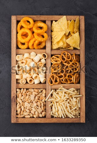 Various snacks in vintage wooden box. Onion rings,nachos, salty peanuts with potato sticks and pretz Stock photo © DenisMArt