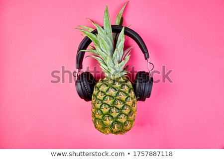 Flat lay of trendy, funny face pineapple fruit with headphones and sunglasses. Stock photo © Illia
