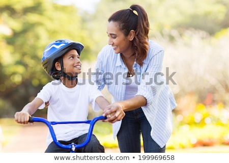 pretty boy on a bike outside stock photo © oleksandro