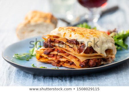 dish of lasgane with salad leaves and italian bread stock photo © monkey_business