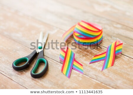 gay awareness ribbon and scissors on wooden boards Stock photo © dolgachov