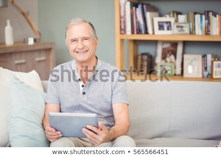 Сток-фото: Front View Of Happy Senior Man With Digital Tablet Looking At Camera With Senior Women On The Backgr