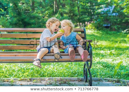 toddlers boy and girl sitting on a bench by the sea and eat an apple stock photo © galitskaya