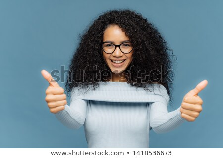 Supportive pleasant looking ethnic girl has bushy dark hair, shows thumbs up, recommends excellent s Stock photo © vkstudio