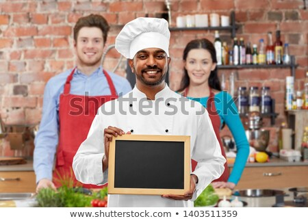 happy indian chef with chalkboard at cooking class Stock photo © dolgachov