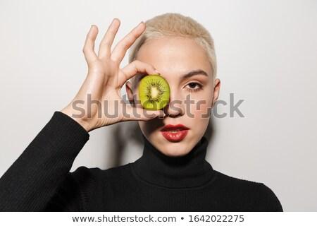 Blonde stylish woman holding kiwi covering eye. Stock photo © deandrobot
