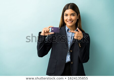 Stock photo: Smiling female entrepreneur showing her business card against a white background