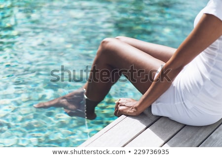 woman resting at pool with feet in water stock photo © kyolshin