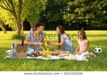 Parents together with little girl have rest in summer garden. Look at girl sitting on lawn. stock photo © Paha_L