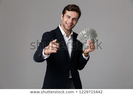 Happy caucasian businessman holding money. Stock photo © RAStudio