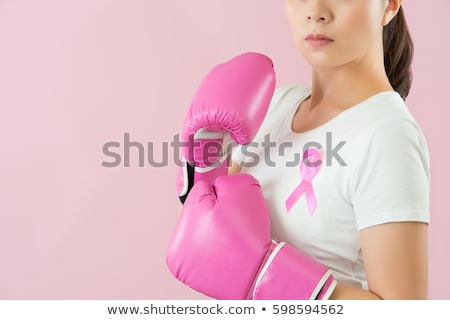 Standing woman for breast cancer awareness in boxing gloves on white background Stock photo © wavebreak_media