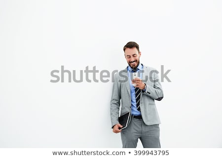 happy businessman using his phone in the office stock photo © minervastock