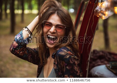 Image of joyful woman, wearing hippy accessories smiling while r Stock photo © deandrobot