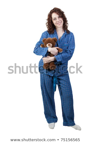 A beautiful young woman wearing pajamas hugging her stuffed teddy bear Stock photo © ruslanshramko