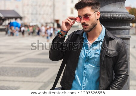 portrait of curious casual man fixing red sunglasses in city stock photo © feedough
