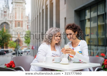 daughter and senior mother with smartphone at cafe stock photo © dolgachov