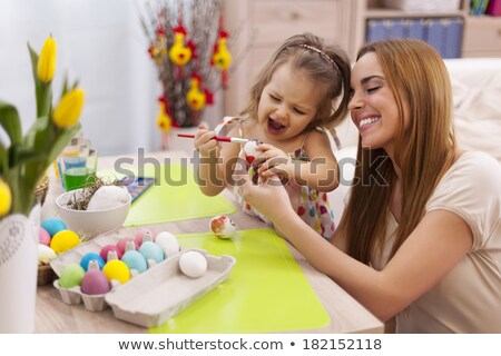 girl decorating willow by easter eggs at home Stock photo © dolgachov