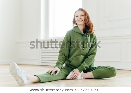 Sport and motivation concept. Fit slim ginger Caucasian female in sportswear, stretches legs, has mo Stock photo © vkstudio