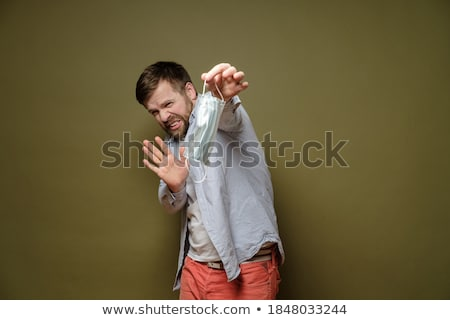 Caucasian man in respiratory medical mask show stop gesture to spreading world pandemic of covid-19 Stock photo © robuart