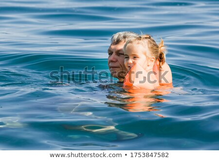 Grandfather in pool holds granddaughter on shoulders Stock photo © Paha_L