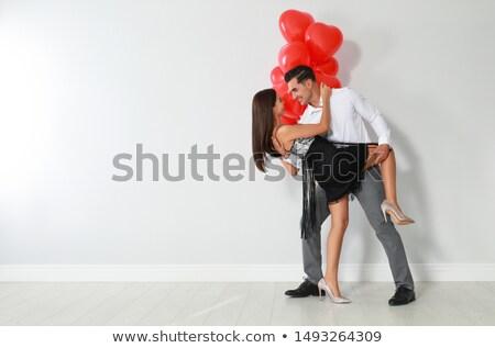 smiling woman showing red dress to boyfriend stock photo © wavebreak_media