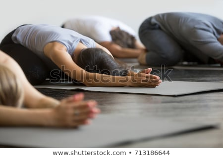 Instructor with student practicing child pose in yoga studio stock photo © wavebreak_media