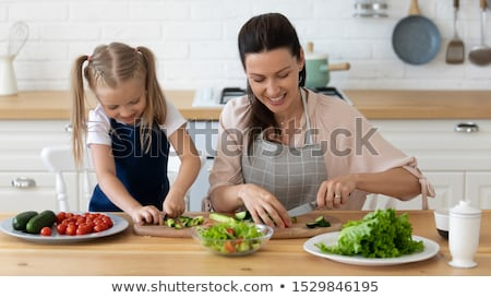 Smiling Woman Cutting Vegetables On Chopping Board Stock photo © AndreyPopov