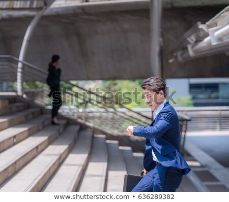 worried young businessman running late stock photo © deandrobot