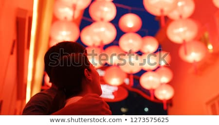 Woman celebrate Chinese New Year look at Chinese red lanterns. Chinese lanterns are reflected in gla Stock photo © galitskaya