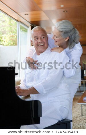 Side view of active senior man and senior woman performing stretching exercise on exercice ball in t Stock photo © wavebreak_media
