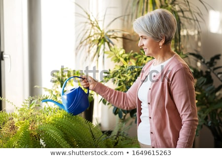 Happy senior woman watering can at home Stock photo © Andersonrise
