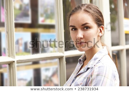 disappointed young woman looking in window of estate agents stock photo © highwaystarz