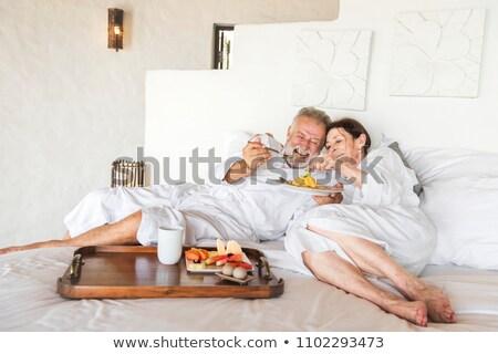 érett pár ágy fürdőköpeny nő kezek Stock fotó © photography33