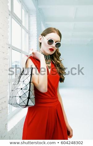Nő vörös ruha néz kézitáska portré izolált Stock fotó © deandrobot