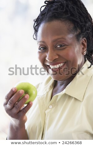 senior woman eating green apple and smiling at the camera stock photo © monkey_business