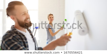 happy young woman painting wall focus on the roller stock photo © taiga