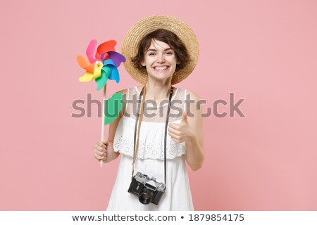 Woman holding toy windmill up in the air Stock photo © IS2