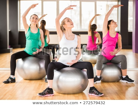 happy pregnant women exercising at gym yoga stock photo © dolgachov