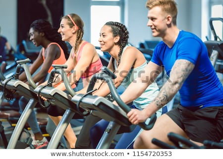 side view of a fit happy woman cycling during cardio workout routine at the gym stock photo © kzenon