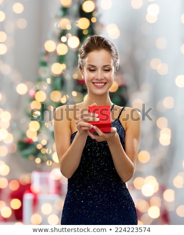 woman with red gift box over christmas tree lights Stock photo © dolgachov